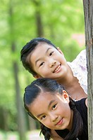 Two girls hiding behind a tree together and looking at the camera