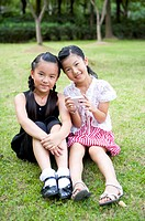 Two girls sitting on the lawn together and looking at the camera with smile