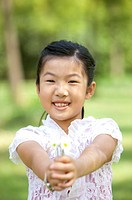 Girl holding flowers and smiling at the camera (thumbnail)
