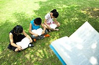Three children sitting on the lawn with book and learning together