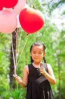 Girl eating ice cream and holding balloons
