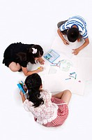 Child, Three children sitting and drawing on the floor together (thumbnail)