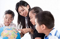 Child, Young teacher and students looking at the globe together (thumbnail)