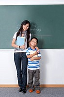 Child, Young teacher and boy standing and holding book in the classroom