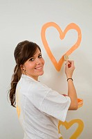 Young woman paints hearts on a wall