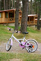 Children pink bicycle in wooden cabin mountain pine camping Pyrenees