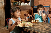 Guarani children eating, in the poor area of Chacarita, Asuncion, Paraguay, South America