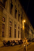 Cyclist and people at a sidewalk cafe at night, Residenz street, Odeonsplatz, Munich, Germany, Europe