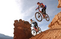 Two men on mountain bikes riding over rocks, Gooseberry Trail, Zion National Park, Springdale, Utah, USA