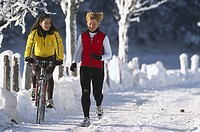 Woman riding a bike next to jogger on a snowy road, Ramsau, Styria, Austria, Europe
