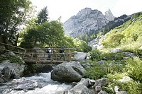 Couple walking on wooden foot bridge, Val di Mello Pizzo Cacciabello in back, Brengalia Mountains, Italy