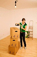 Young woman moves into her new home and drinks a glass of champagne