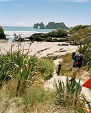 Mother with children hiking at Wharariki Beach, northwest coast, South Island, New Zealand
