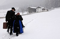Farmer and mother walking through the snow towards farmhouse, Agriculture, South Tyrol, Italy