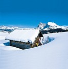 People sunbathing behind a snow covered alpine hut, Alpe di Siusi, Valle Isarco, South Tyrol, Italy, Europe