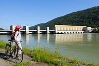 Female cyclist near river Danube, Run_of_the_river hydroelectricity Jochenstein, Danube Cycle Route Passau to Vienna, Upper Austria, Austria