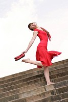 young woman in a red dress, barefooted on stairs