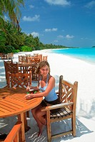 young woman sitting in a bar at the beach, enjoying a cocktail, Maldives, Indian Ocean