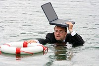 businessman in deep water holdig laptop over his head and grabbing to life belt