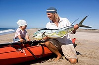 A man showing his little daughter his recently caught mahi_mahi, Punta Conejo, Baja California Sur, Mexico, America