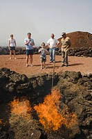 Demonstration of fire by volcanic heat with brushwood, Parque Nacional de Tiimanfaya, Montanas del Fuego, park ranger, family, UNESCO Biosphere Reserv...