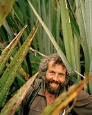 Trapper Bruce Reay amidst flax plants at Westland National Park. west coast, South Island, New Zealand
