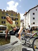 Young woman sitting at the fountain after a bike tour, village square, Glurns, Vinschgau, South Tyrol, Italy
