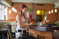 young woman sitting in a cafeteria at a laptop drinking a coffee