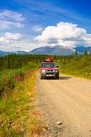 Car travelling on Nabesna Road in Wrangell Saint Elias National Park with the Mentasta Mountains in the background, Southcentral Alaska, Summer