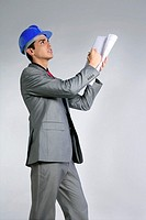 Architect engineer with blue hardhat and suit isolated on gray