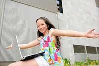 Beautiful brunette little girl teen expression with laptop city outdoor