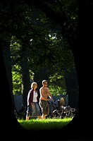 Couple walking in forest with pram / buggy on a sunny day, Denmark