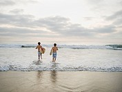Boys running in surf
