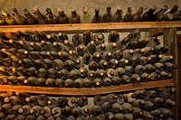manor Els Calderers, dusty bottles of wine in a storage rack in the wine cellar, Spain, Balearen, Majorca, Sant Joan