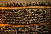 manor Els Calderers, dusty bottles of wine in a storage rack in the wine cellar, Spain, Balearen, Majorca, Sant Joan