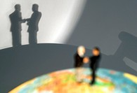 symbolic for international economic relations: little figures on a globe shaking hands