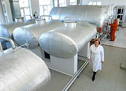 Distillery filtering room. Worker walking past tanks in the filtering area of a vodka and brandy distillery. This is the Yuzhnaya Stolitsa vodka and b...