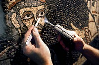 Mosaic restoration. Archaeologist using a microjet and scalpel to restore a mosaic found in the medieval abbey of Saint_Bertin, France. Restoration of...