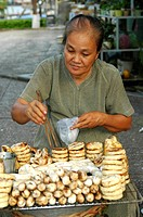 Sales woman selling deep_fried bananas Can Tho Mekong delta Viet Nam