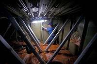 Passenger aircraft construction. Technician in the central fuel tank of an Airbus passenger plane installing the struts that will brace the structure....