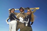two women in skiing clothes haunting a man with ski, Austria, Styria