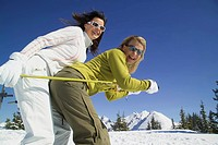 two young women in skiing clothes standing in snow with ski sticks, Austria, Styria