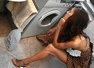 young woman sitting and waiting in front of her washing machine