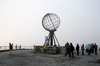 Tourists in front of a globe, fog, North Cape, Norway