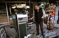 Turkish businessman on a shopping street of Aleshir, Turkey, at its coffee roasting machine.