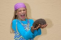 western hedgehog, European hedgehog Erinaceus europaeus, girl crying in pain in the moment she is bitten by the hedgehog on her hand, Germany