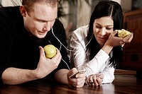 Young couple listening to music together and eating an apple