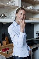 A woman eating a piece of red pepper in the kitchen