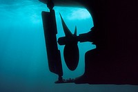 Motorboat hull and propeller seen from underwater