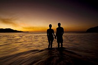 Silhouette of young couple holding hands on the beach while watching the sunset in Playas del Coco, Costa Rica
